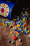 Antique Marble Collection. A collection of colorful antique glass marbles spilling out of an antique metal tin onto a wooden floor Stock Images