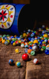 Antique Marble Collection. A collection of colorful antique glass marbles spilling out of an antique metal tin onto a wooden floor Royalty Free Stock Photo