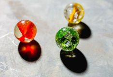 Antique Marble Collection. Three colorful glass antique marbles on a metal background Royalty Free Stock Photo
