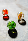 Antique Marble Collection. Three colorful glass antique marbles on a metal background Stock Photo