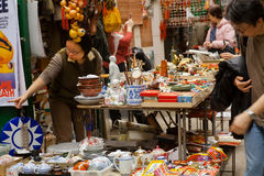 Antique market trader showing some crockery and old statues for customers Stock Photo