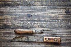 Antique Meat Fork and Butcher`s Knife. Over top a rustic wood table / background. Image shot from overhead view stock photo