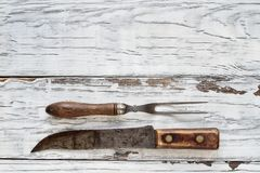 Antique Meat Fork and Butcher`s Knife on White Background. Vintage meat fork and butcher`s knife over top a rustic wood table / background. Image shot from royalty free stock photo