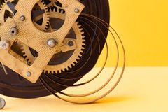 Antique mechanic clockwork mechanism, spring bronze cogs wheels macro view. Shallow depth of field, selective focus. Yellow colorful background Royalty Free Stock Photos