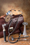 Antique medical instruments. Doctor's bag and antique medical instruments such as stethoscope, reflex hammer and head mirror royalty free stock photography