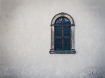 Antique medieval window with iron bars and old white wall Royalty Free Stock Image