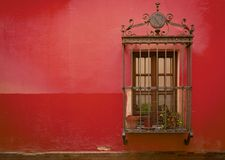 Antique medieval window with rusty iron bars and Red Pear wall. Antique medieval window with rusty iron bars and Red Pear orange wall in old Santa cruz quarter royalty free stock images