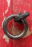 Antique Metal Door Handle. Old, round door handle on a wood door with chipped red paint Stock Photos