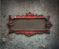 Antique metal frame. Antique old bronze metal frame painted cracked red paint with screws on stone wall with room for your text Stock Photos