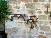 Antique metal objects are hanging on a stone wall. Stock Image
