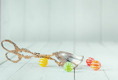 Antique metal tongs and round colorful candies. Low-angle view of an antique and ornate metal tongs close to round colorful candies over a white wooden Stock Photo
