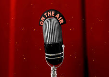 Antique Microphone. An Antique Microphone used in old-timed broadcasting. Image is set against a red velvet curtain with magic sparks around Stock Photos