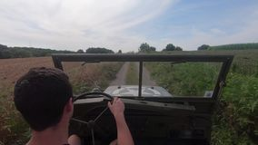 Military 4X4 car driving on dirt road. A antique military 4X4 car driving on dirt road stock video footage