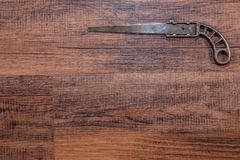 Antique miniature metal saw on a hardwood workbench - top right Royalty Free Stock Photo
