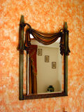Antique Mirror. A beautiful antique mirror on an orange wallpapered wall Royalty Free Stock Photo