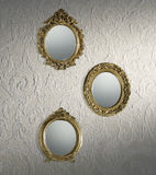 Antique mirrors wallpaper. Antique oval mirrors on a wall with antique textured wallpaper royalty free stock photos