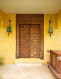Antique Moroccan style wooden door on yellow wall Royalty Free Stock Photography