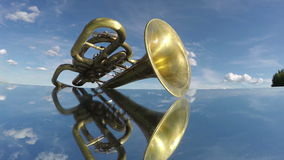 Antique musical wind brass instrument on mirror and clouds. Timelapse 4K stock footage