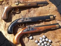 Antique muzzle-loader pistols. Black and brown antique muzzle-loader pistols at a reenactment show royalty free stock photos
