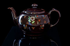 Antique Native American Teapot on Black. This antique Native American teapot is a dark brown with Indian artwork decorating this old glassware.  It has a black Royalty Free Stock Photos