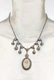 Antique necklace with cameo pendant. Antique cameo and diamond necklace on white background stock image