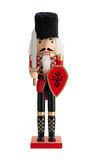 Antique Nutcracker Guard isolated. Antique Nutcracker Guard with a sword and red shield. He has white hair and beard. He sports a black bearskin fur hat, with a Royalty Free Stock Image