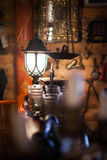 Antique objects in dim light. Antiques in dim light. Old antique book, glass, lamp Royalty Free Stock Images
