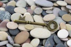 Antique old brass key on beach stones Stock Image