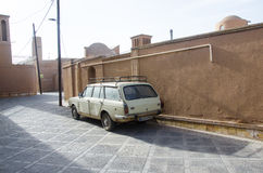 Antique. Old car parked near a historic house in Yazd, Iran. The car is of Peykan brand which was made in Iran until 2005 Stock Images