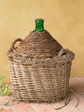 Antique old demijohn, carboy, by yellow wall. Stock Photography