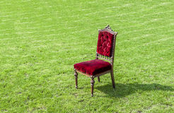 Antique old red chair on green grass, abstract background. Royalty Free Stock Photos