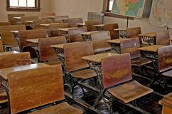 Antique Old School Classroom. This photo is an antique, turn of the century old school classroom with the wooden desks, wood floors, old radiator and vintage Royalty Free Stock Photography