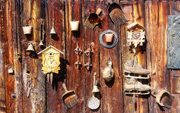 Antique old style retro object assemblage on a wooden wall. rustic stile. Rake in blueberries, clock, bell, art, old Stock Photography