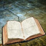 Antique open book on cracked surface Royalty Free Stock Photo