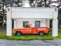 Antique orange pickup trunk parked under building Stock Photos
