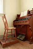 Antique Organ. And chair on a wooden floor stock photography