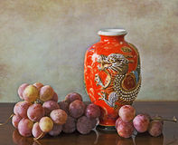 Antique oriental red vase and grapes Stock Photography
