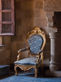 Antique ornate armchair in castle setting. Antique Chair from Palace in Rhodes, Greece.  Owned by Mussolini during Italian occupancy during WW2 Royalty Free Stock Photos