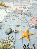 Antique pacific map with shells. An old vintage map of the asia pacific region, taken with some sea shells, starfish, and a pencil.  Travel and geography concept Stock Photo