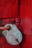 Antique Padlock. Antique brass padlock on vivid red-painted door. Lots of rust and textures stock photography