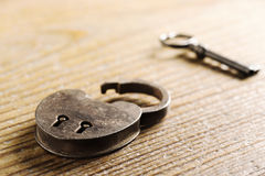 Antique Padlock with key. On wooden table royalty free stock images