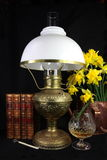Antique Paraffin Lamp still life. A still life of an antique brass paraffin lamp circa 1880 with antique leather books, antique bookmark, daffodils in an antique stock photography