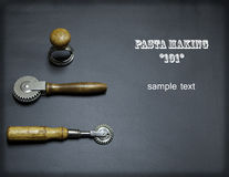 Antique Pasta Making Tools Layout. Antique pasta making tools on a black chalkboard background; pastry sealer, pasta cutter, and ravioli stamp; possible magazine Royalty Free Stock Image
