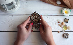 Antique pendant in the girl hands  on a white background wooden. Table Royalty Free Stock Image