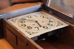 Antique pendulum clock restoration. An antique pendulum clock on a wood table Stock Images