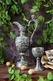 Antique pewter. Antique pitcher and a goblet as well as walnuts on a dark background Royalty Free Stock Photography