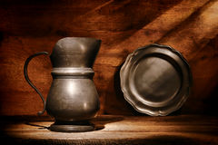 Antique Pewter Pitcher and Plate on Old Wood Shelf Royalty Free Stock Photo