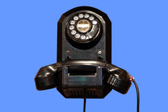 Antique phone. Antique telephone (isolated on blue Royalty Free Stock Image