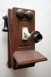 Antique Phone. An antique phone hangs on a white wall Royalty Free Stock Photo