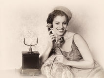 Antique phone call. Stunning vintage 1920s woman talking on an antique telephone Stock Photos